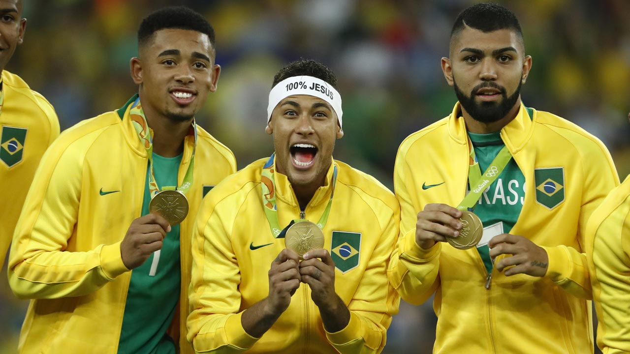 Brazil's players including Neymar (C) celebrate on the podium during the medal presentation following the Rio 2016 Olympic Games men's football gold medal match between Brazil and Germany at the Maracana stadium in Rio de Janeiro on August 20, 2016. PHOTO: Odd Andersen / AFP