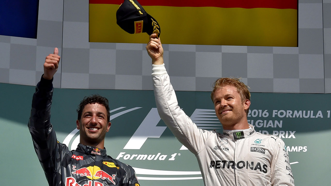 Mercedes AMG Petronas F1 Team's German driver Nico Rosberg (2R) celebrates winning next to second placed Red Bull Racing's Australian driver Daniel Ricciardo after the Belgian Formula One Grand Prix at the Spa-Francorchamps circuit in Spa on August 28, 2016. LOIC VENANCE / AFP