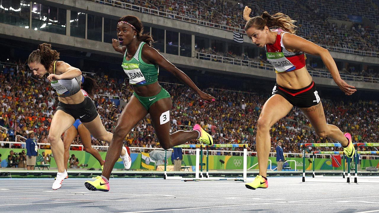(L-R) Germany's Nadine Hildebrand, Nigeria's Oluwatobiloba Amusan and Switzerland's Clelia Reuse-Rard compete in the Women's 100m Hurdles Semifinal during the athletics event at the Rio 2016 Olympic Games at the Olympic Stadium in Rio de Janeiro on August 17, 2016. Adrian DENNIS / AFP