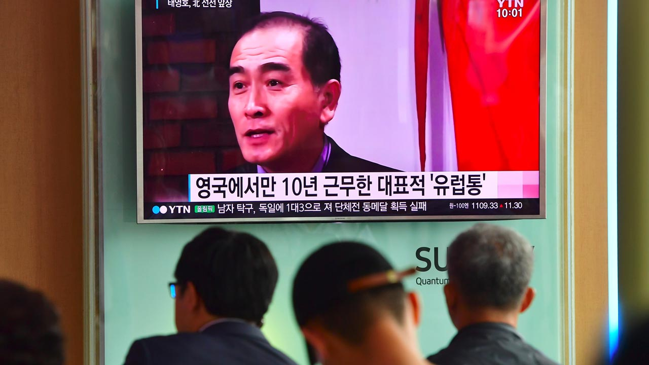 People watch a television news broadcast showing file footage of Thae Yong-Ho, North Korea's deputy ambassador to Britain, at a railway station in Seoul on August 18, 2016. South Korea said on August 17 that North Korea's deputy ambassador to Britain had defected to Seoul, in a rare and damaging loss of diplomatic face for Pyongyang. PHOTO: JUNG YEON-JE / AFP