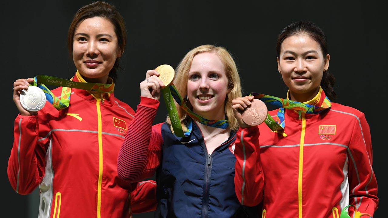 USA's gold medallist Virginia Thrasher (C) poses on the podium with China's silver medal winner Du Li (L) and China's bronze medallist Yi Siling during the medal ceremony for the women's 10m air rifle shooting event at the Rio 2016 Olympic Games at the Olympic Shooting Centre in Rio de Janeiro on August 6, 2016. Pascal GUYOT / AFP