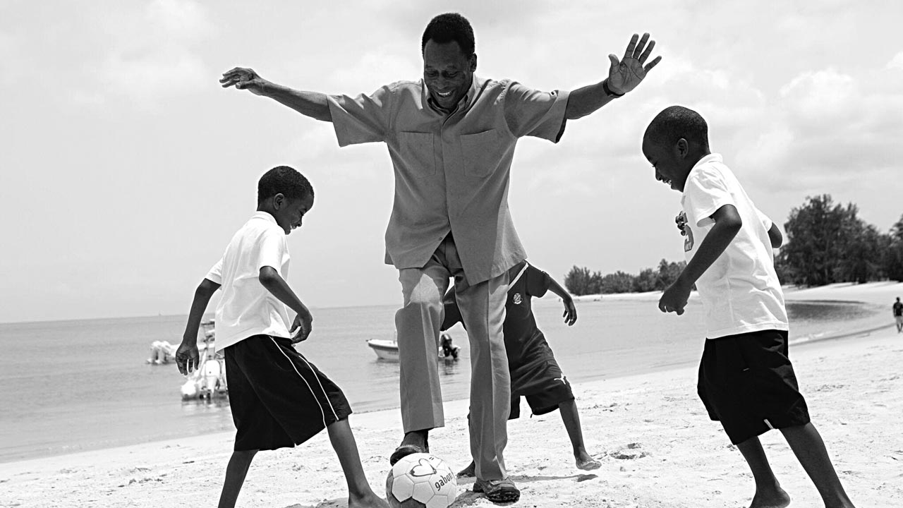 Pele displaying soccer skills with Brazilian kids