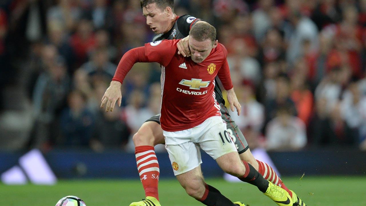 Southampton's Danish midfielder Pierre-Emile Hojbjerg vies with Manchester United's English striker Wayne Rooney (R) during the English Premier League football match between Manchester United and Southampton at Old Trafford in Manchester, north west England, on August 19, 2016. Oli SCARFF / AFP