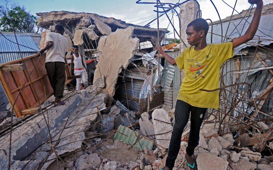 Residents move furniture through debris and building rubble after a building collapsed in Mogadishu's Shangani district on August, 30, 2016.  A refugee mother and one of her children died after their house inside an internally displaced persons (IDPs) settlement collapsed.  / AFP PHOTO / MOHAMED ABDIWAHAB