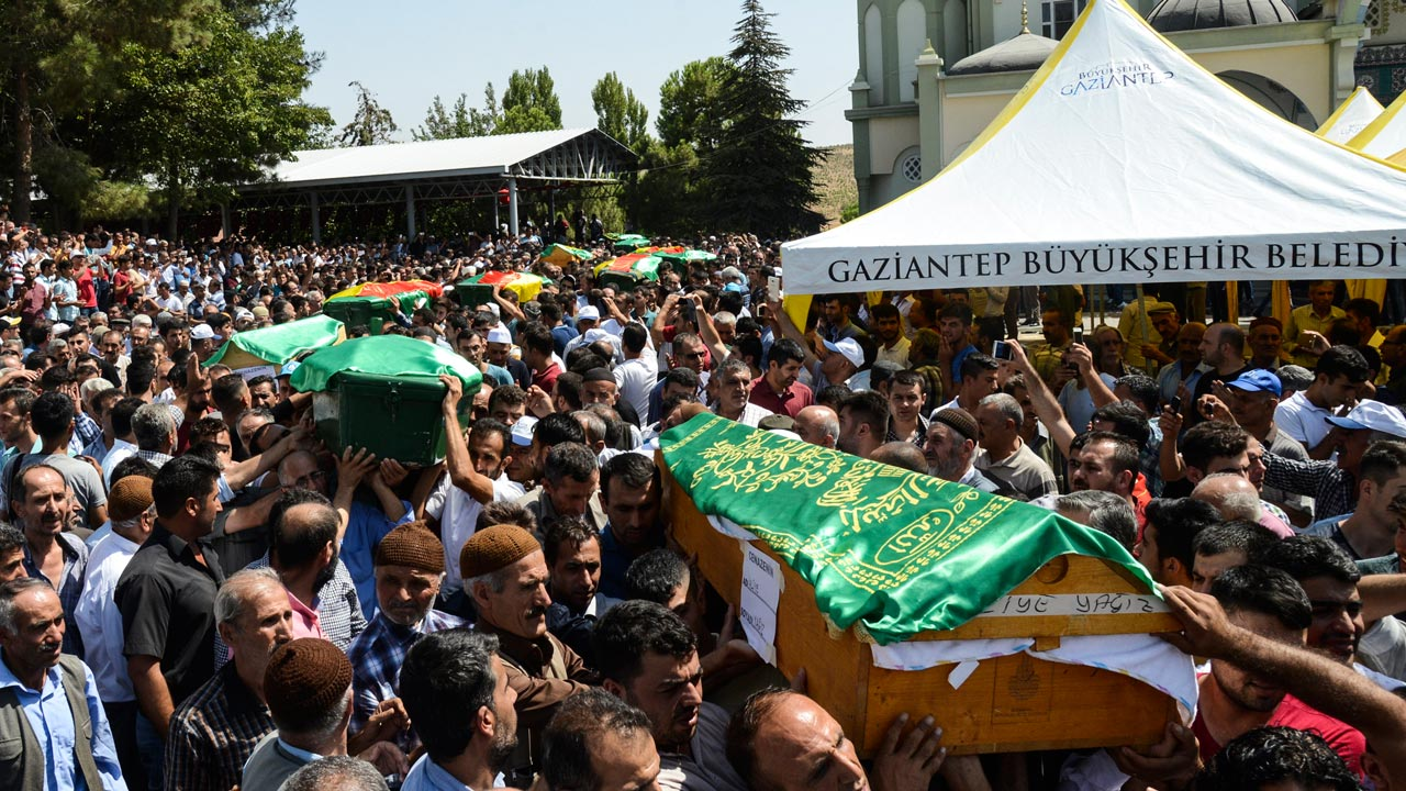 """People carry coffins during a funeral for victims of last night's attack on a wedding party that left 50 dead in Gaziantep in southeastern Turkey near the Syrian border on August 21, 2016. At least 50 people were killed when a suspected suicide bomber linked to Islamic State jihadists attacked a wedding thronged with guests, officials said on August 21. Turkish President Recep Tayyip Erdogan said the IS extremist group was the """"likely perpetrator"""" of the bomb attack, the deadliest in 2016, in Gaziantep late Saturday that targeted a celebration attended by many Kurds. PHOTO: ILYAS AKENGIN / AFP"""