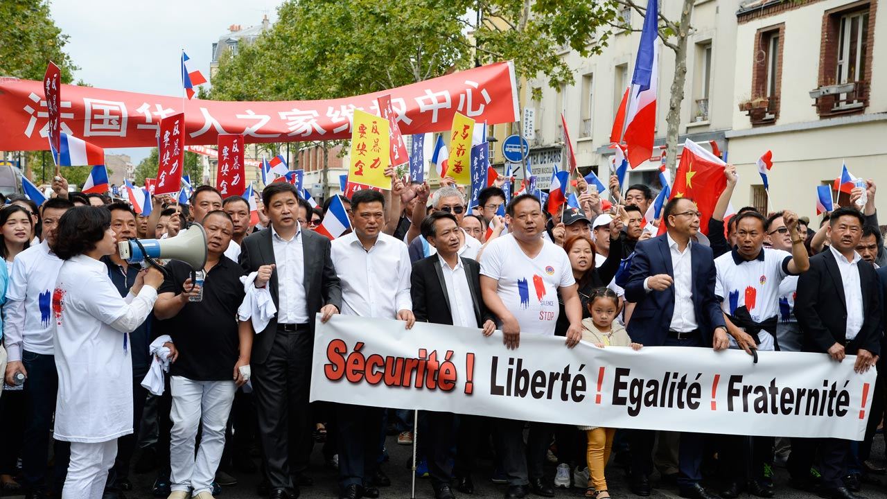 "FILES) This file photo taken on August 21, 2016 shows people holding a banner reading ""Security, Freedom, Equality, Brotherhood"" during a demonstration in Paris organised by several associations of the Chinese community to ask for protection measures, after the death of Zhang Chaolin killed on August 7, 2016. Shocked by the deadly assault of one of its members in Paris suburb, the Chinese community is mobilized to demand ""safety for all"", prompting authorities to react, especially as some are tempted to act the part of justice. BERTRAND GUAY / AFP"