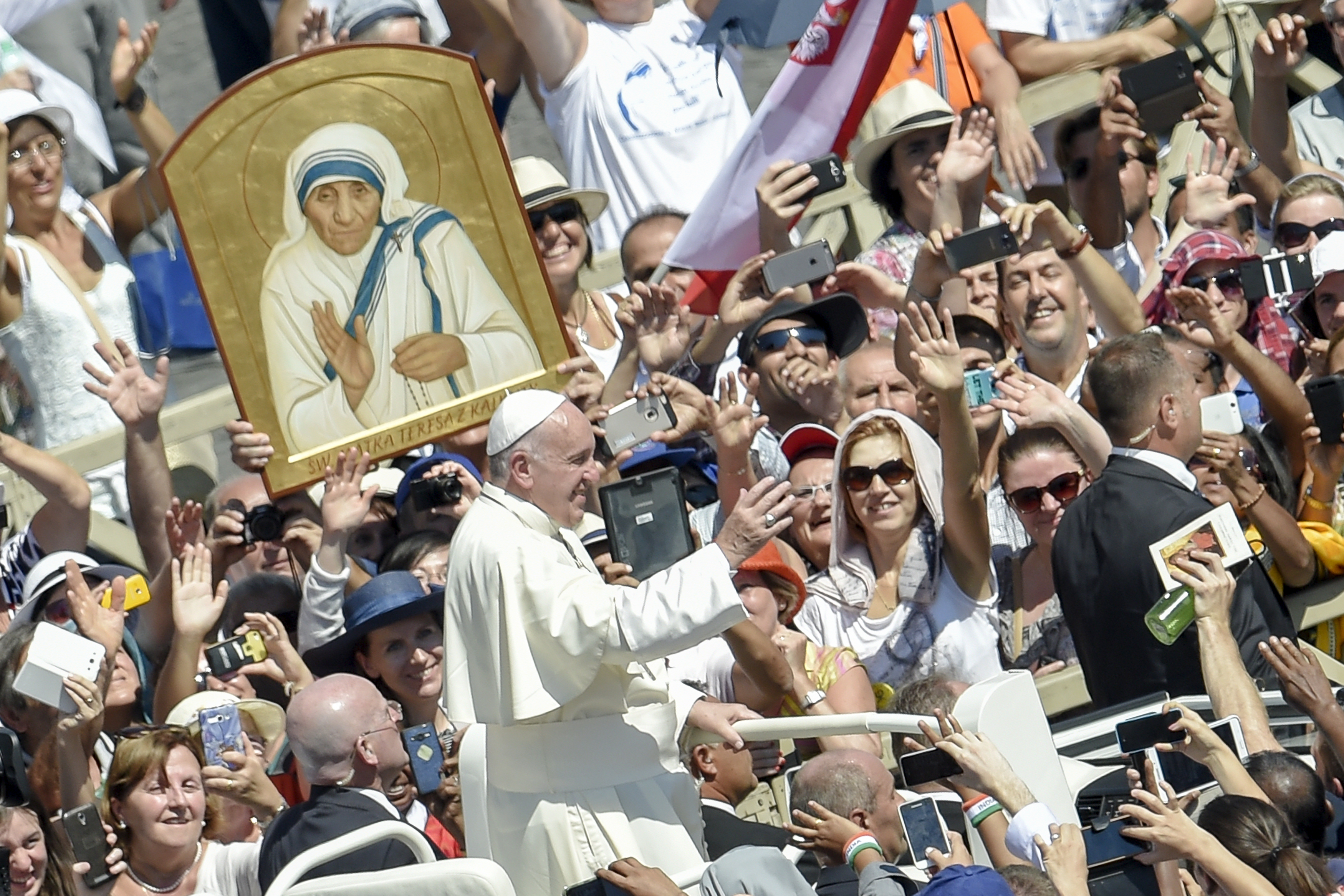 Pope Francis (C) waves to faithful as he leaves after a Holy Mass and the canonisation of Mother Teresa of Kolkata, on Saint Peter square in the Vatican, on September 4, 2016. Mother Teresa, the nun whose work with the dying and destitute of Kolkata made her a global icon of Christian charity, was made a saint on September 4, 2016. Her elevation to Roman Catholicism's celestial pantheon came in a canonisation mass in St Peter's square in the Vatican that was presided over by Pope Francis in the presence of 100,000 pilgrims. ANDREAS SOLARO / AFP