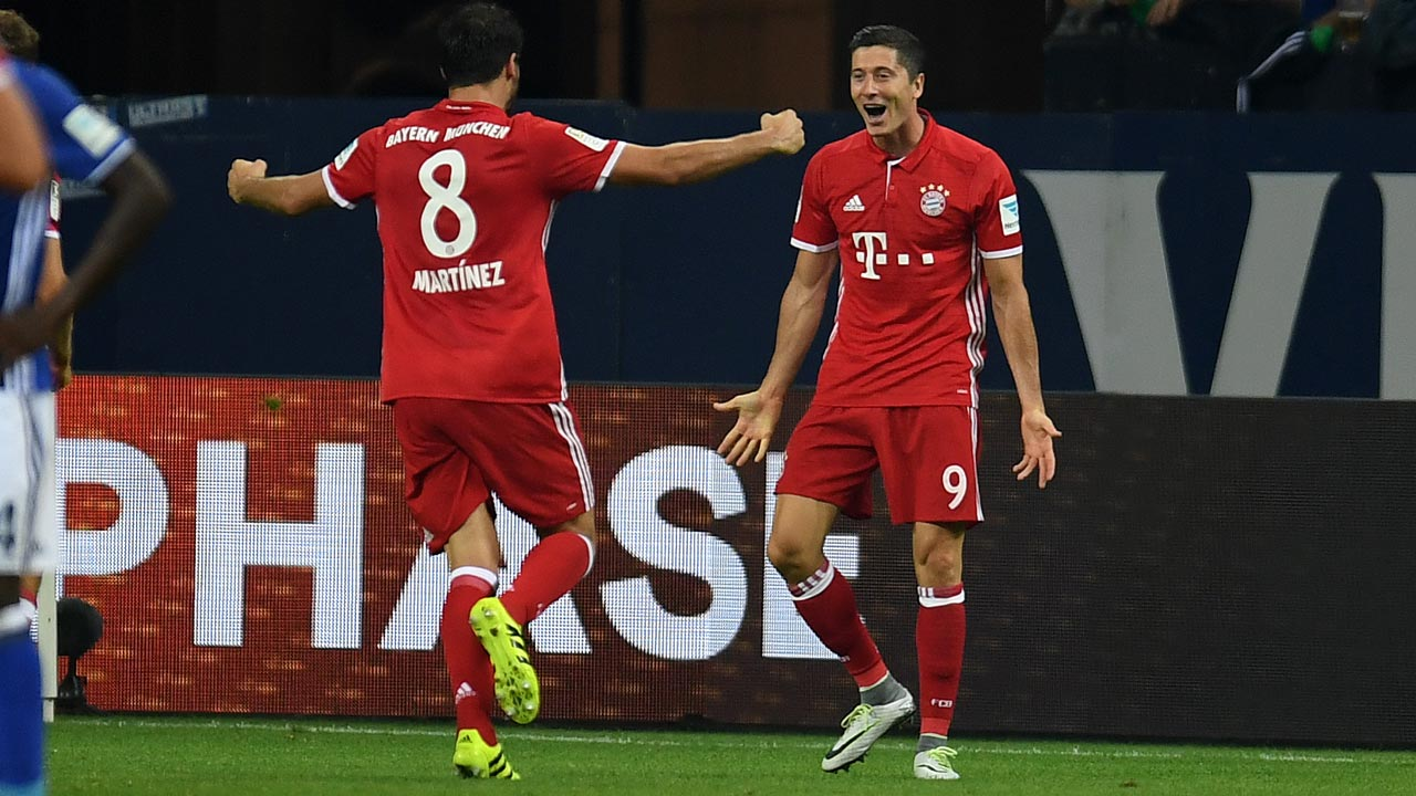 Bayern Munich's Polish striker Robert Lewandowski (R) celebrate scoring the opening goal with Spanish teammate Javier Martinez during the German first division Bundesliga football match between Schalke 04 and FC Bayern Munich in Gelsenkirchen, western Germany on September 9, 2016. PATRIK STOLLARZ / AFP
