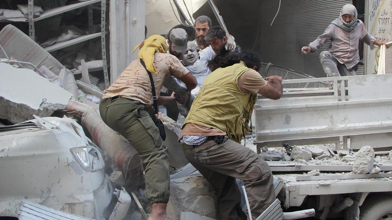 Syrian men evacuate a victim from the rubble of a building following a reported air strike on the rebel-held northwestern city of Idlib on September 10, 2016. More than 290,000 people have been killed in Syria since its conflict erupted in March 2011, and millions displaced by the fighting. Omar haj kadour / AFP