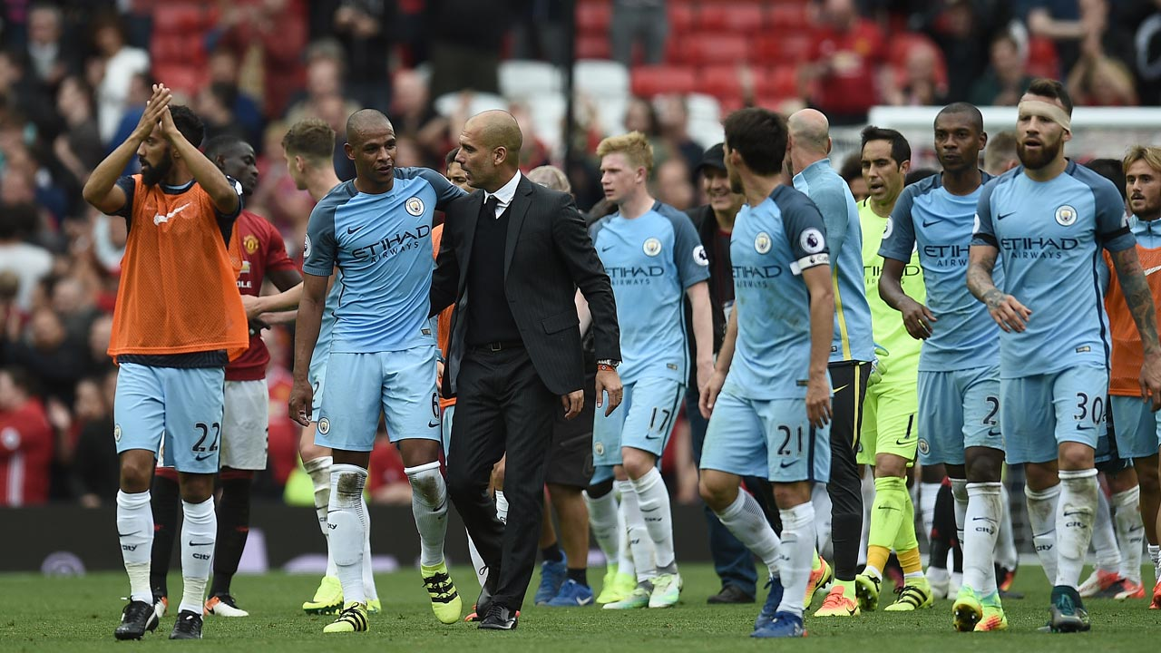 Manchester City's Spanish manager Pep Guardiola and his players celebrate on the pitch after the English Premier League football match between Manchester United and Manchester City at Old Trafford in Manchester, north west England, on September 10, 2016. Pep Guardiola savoured a derby success over arch-rival Jose Mourinho on Saturday as Manchester City beat Manchester United 2-1 in an engrossing Premier League clash. Oli SCARFF / AFP