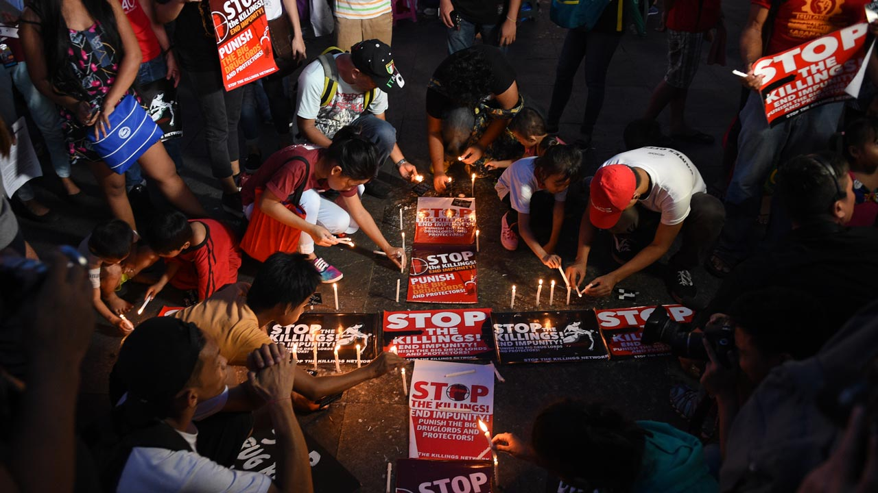 Activists hold a candle light vigil for victims of the extra judicial killings in the drug war of the government in front of a church in Manila on September 16, 2016. The Philippines faced calls September 16 to investigate its firebrand president after a self-confessed hitman alleged Rodrigo Duterte ordered a thousand opponents and suspected criminals murdered when he was a city mayor. TED ALJIBE / AFP
