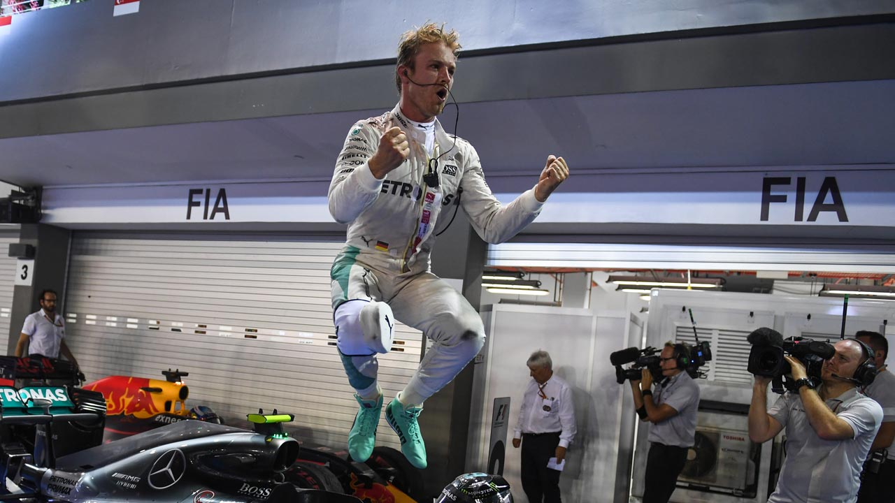 Mercedes AMG Petronas F1 Team's German driver Nico Rosberg jumps from his car as he celebrates winning the Formula One Singapore Grand Prix in Singapore on September 18, 2016. Mohd Rasfan / AFP