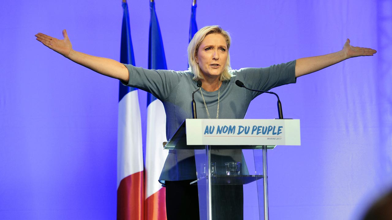 "French far-right Front National (FN) party's President, Marine Le Pen, gestures as she delivers a speech on stage during the FN's summer congress in Frejus, southern France, on September 18, 2016. Marine Le Pen's slogan reading ""In the name of the [French] people"" is seen on the rostrum. Franck PENNANT / AFP"