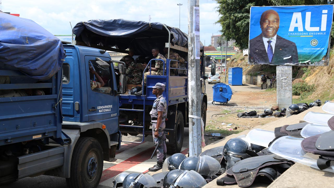 Gabonese security forces are seen deployed next to a campaign poster of President Ali Bongo in Libreville ahead of the Constitutional Court's announcement on September 23, 2016 on who will be the country's next president. The streets of Libreville emptied rapidly on September 23 with residents fearing a new bout of bloodshed as the Constitutional Court prepared to rule on who will be Gabon's next president following a bitterly-contested election. Across the nation, there is widespread concern that a ruling in favour of President Ali Bongo, who won by a wafer thin margin provoking charges of fraud, could spark a fresh wave of furious opposition protests like those which followed the announcement of his victory. Samir TOUNSI / AFP