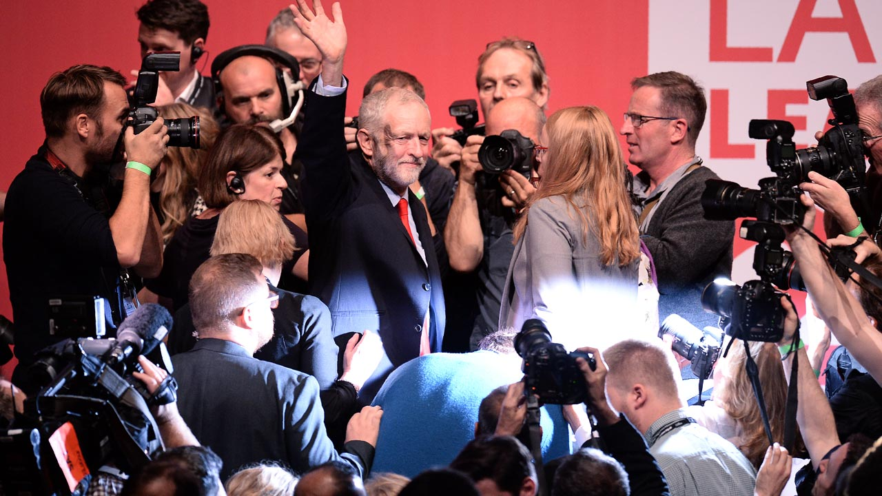 British opposition Labour Party leader Jeremy Corbyn (C) waves following his speech after being announced as the winner of the party's leadership contest at the Labour Party Leadership Conference in Liverpool on September 24, 2016. OLI SCARFF / AFP