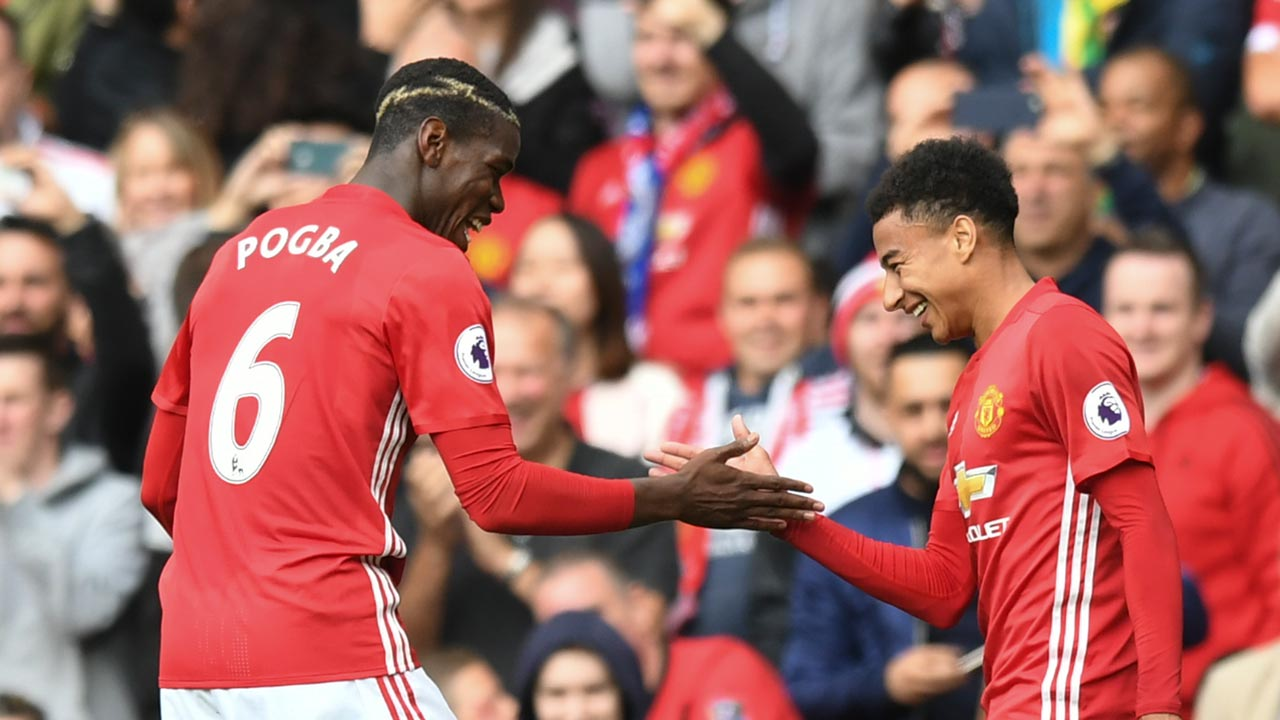Manchester United's French midfielder Paul Pogba (L) and Manchester United's English midfielder Jesse Lingard (R) celebrate after Pogba scored their fourth goal during the English Premier League football match between Manchester United and Leicester City at Old Trafford in Manchester, north west England, on September 24, 2016. ANTHONY DEVLIN / AFP