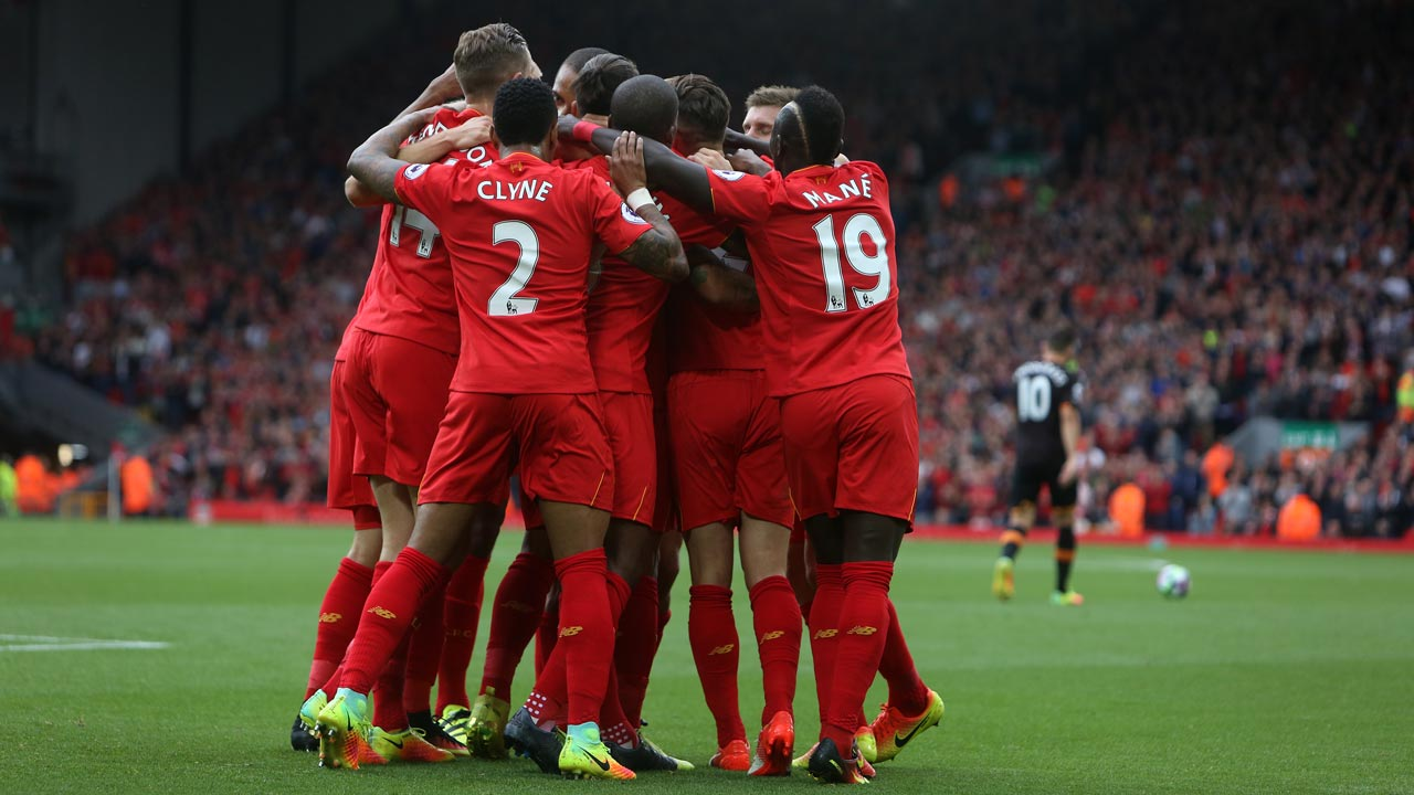 Liverpool's English midfielder Adam Lallana (unseen) is mobbed by teammates after scoring his team's first goal during the English Premier League football match between Liverpool and Hull City at Anfield in Liverpool, north west England on September 24, 2016. Geoff CADDICK / AFP