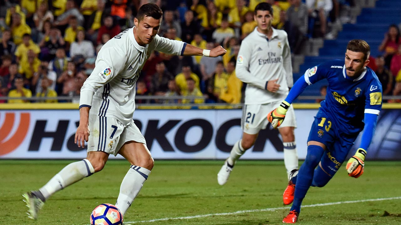 Real Madrid's Portuguese forward Cristiano Ronaldo (L) vies withLas Palmas' goalkeeper Raul Lizoain Cruz (R) during the Spanish league football match UD Las Palmas vs Real Madrid CF at the Gran Canaria stadium in Las Palmas de Gran Canaria on September 24, 2016. DESIREE MARTIN / AFP