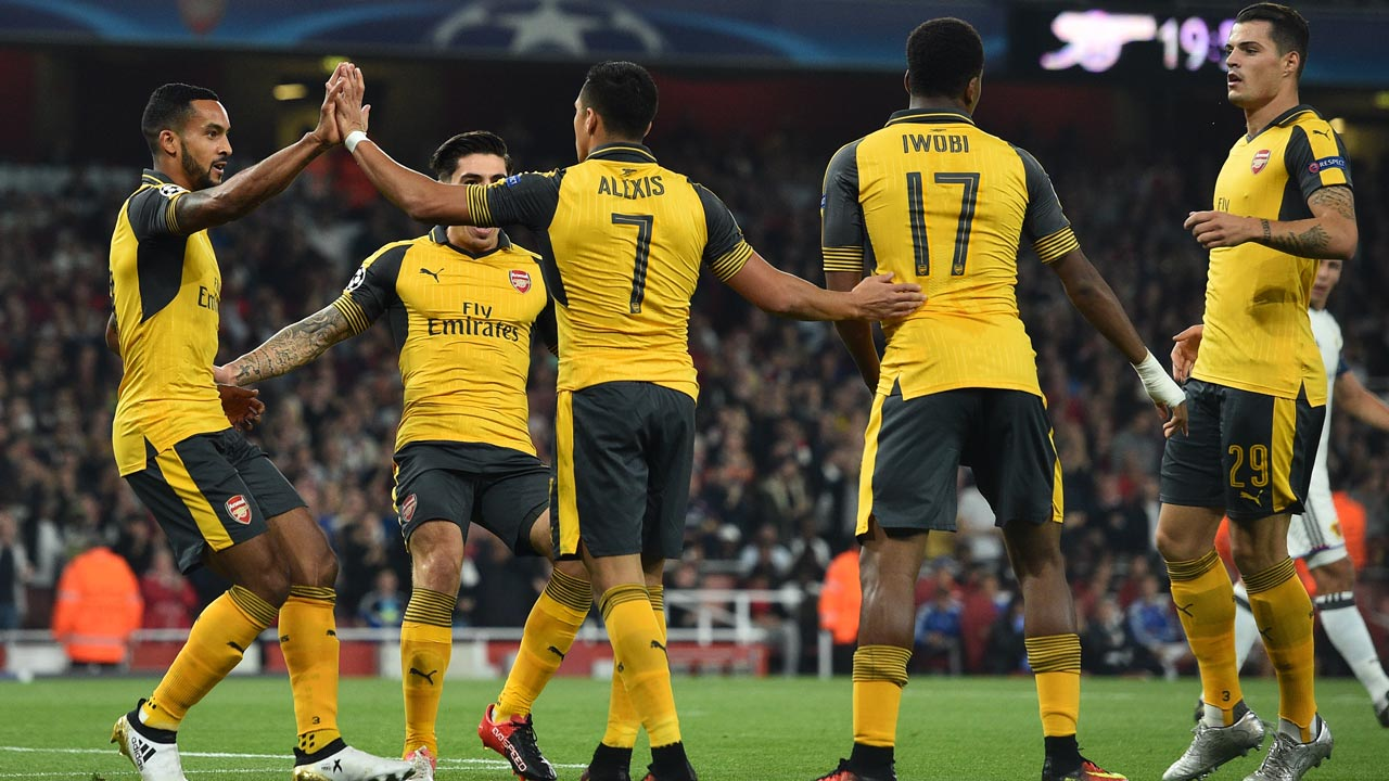 Arsenal's English midfielder Theo Walcott (L) celebrates with teammates after scoring the opening goal of the UEFA Champions League Group A football match between Arsenal and FC Basel at The Emirates Stadium in London on September 28, 2016. Glyn KIRK / IKIMAGES / AFP