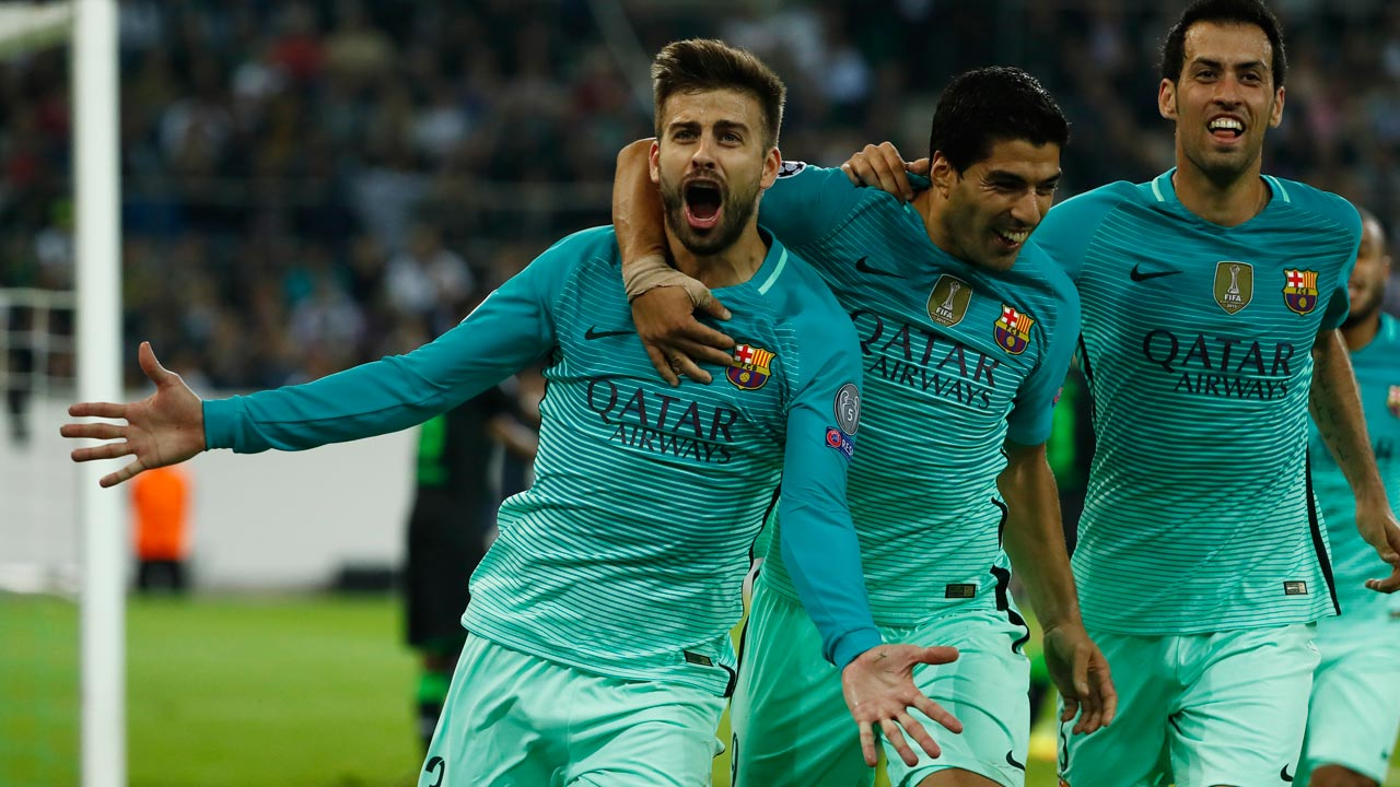 Barcelona's defender Gerard Pique (L) celebrates scoring the 1-2 goal with his teammates Uruguayan forward Luis Suarez and midfielder Sergio Busquets during the UEFA Champions League first-leg group C football match between Borussia Moenchengladbach and FC Barcelona at the Borussia Park in Moenchengladbach, western Germany on September 28, 2016. Odd ANDERSEN / AFP