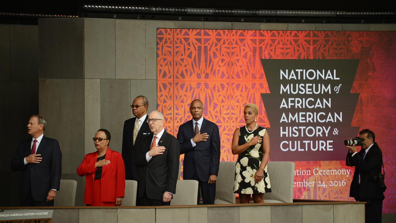 WASHINGTON, DC - SEPTEMBER 24: Dignitaries stand up during the presentation of the colors and the performance of the national anthem during the dedication of the National Museum of African American History and Culture September 24, 2016 in Washington, DC, before the museum opens to the public later that day. The museum is a Smithsonian Institution museum located on the National Mall featuring African American history and culture in the US. Astrid Riecken/Getty Images/AFP Astrid Riecken / GETTY IMAGES NORTH AMERICA / AFP