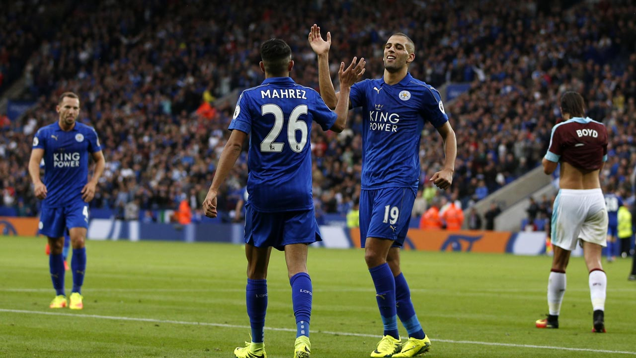 Leicester City's Algerian striker Islam Slimani (R) congratulates teammate Algerian midfielder Riyad Mahrez (C) after the third goal during the English Premier League football match between Leicester City and Burnley at King Power Stadium in Leicester, central England on September 17, 2016. ADRIAN DENNIS / AFP