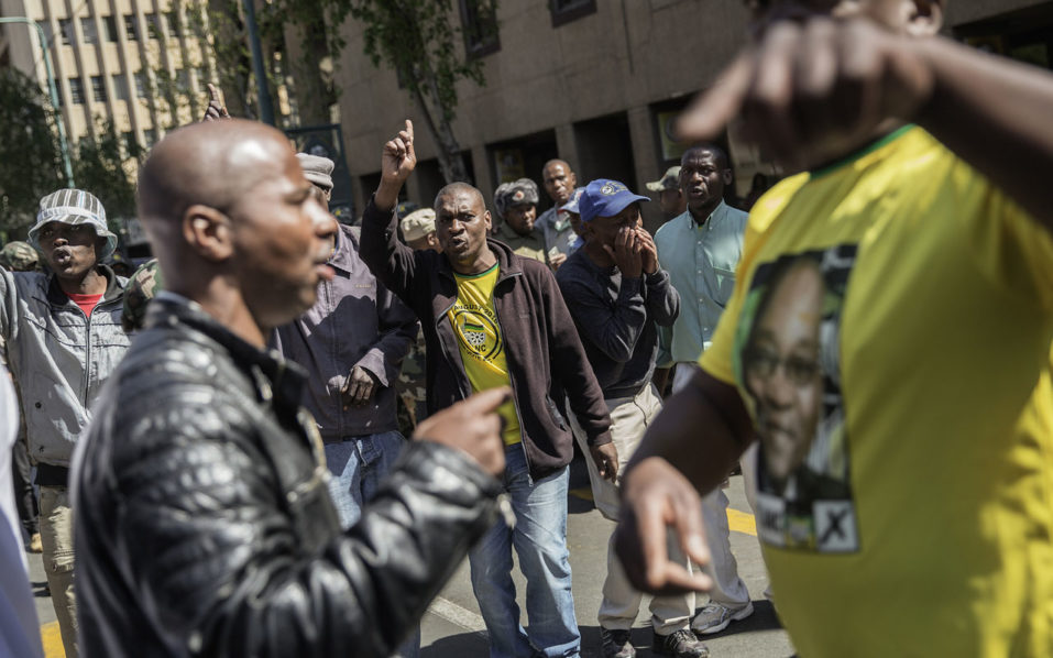 South African ruling party African National Congress President and National Executitve Commitee supporters face off with ANC disgrunteled members demonstrating outside ANC headquarter on Septmber 5, 2016 in Johannesburg, South Africa. Activists from rival factions of South Africa's Africa National Congress (ANC) faced off in central Johannesburg, highlighting deep divisions in the ruling party as pressure grows on President Jacob Zuma. The ANC, which led the struggle to end apartheid, has been rocked by poor recent local election results largely blamed on Zuma's leadership and the country's mounting economic woes. Police surrounded the ANC's Luthuli House headquarters in Johannesburg after some party activists vowed to occupy the building to protest against how the party and government is being run. / AFP PHOTO / GIANLUIGI GUERCIA
