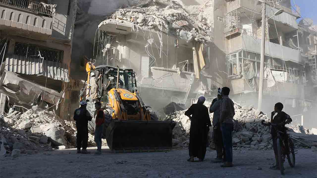 Civilians watch as a tractor clears the rubble following Syrian government forces airstrikes in the rebel held neighbourhood of Tariq a-Bab in Aleppo on September 24, 2016. Residents in Syria's battleground city of Aleppo cowered indoors as fierce air strikes toppled buildings and killed at least 52 civilians, after diplomatic efforts to revive a ceasefire failed. / AFP PHOTO / THAER MOHAMMED