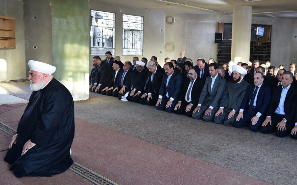 A handout picture released on the Syrian Presidency Facebook page on September 12, 2016, shows Syrian President Bashar al-Assad (4th from R) performing the morning prayer of the Muslim holiday of the Eid al-Adha at a mosque in a government-controlled area of Daraya. / AFP PHOTO / Syrian Presidency Facebook page /