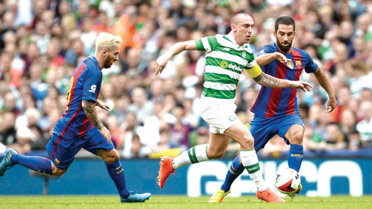 Celtic's, Scott Brown, (middle) with the ball ahead of Messi (left) in Tuesday's champions League game