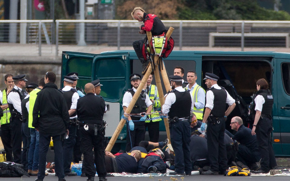 """Emergency services surround protestors from the movement Black Lives Matter after they locked themselves to a tripod on the runway at London City Airport in London on September 6, 2016. Flights at London City Airport have been delayed after Black Lives Matter protesters crossed the dock and """"occupied"""" the runway. / AFP PHOTO / DANIEL LEAL-OLIVAS"""