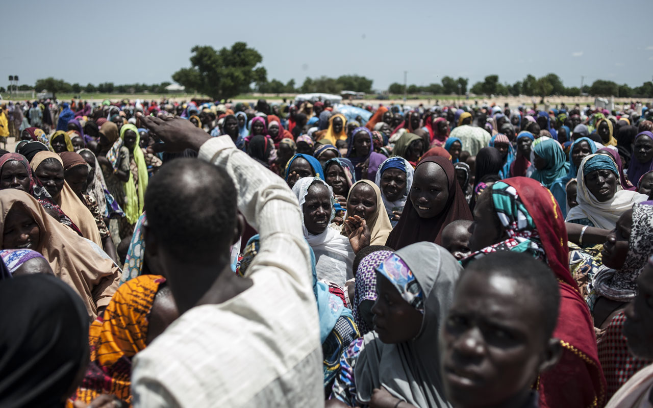 In this photo taken on September 15, 2016 women and children queue to enter one of the Unicef nutrition clinics at the Muna makeshift camp which houses more than 16,000 IDPs (internaly displaced people) on the outskirts of Maiduguri, Borno State, northeastern Nigeria. Aid agencies have long warned about the risk of food shortages in northeast Nigeria because of the conflict, which has killed at least 20,000 since 2009 and left more than 2.6 million homeless. In July, the United Nations said nearly 250,000 children under five could suffer from severe acute malnutrition this year in Borno state alone and one in five -- some 50,000 -- could die. / AFP PHOTO / STEFAN HEUNIS