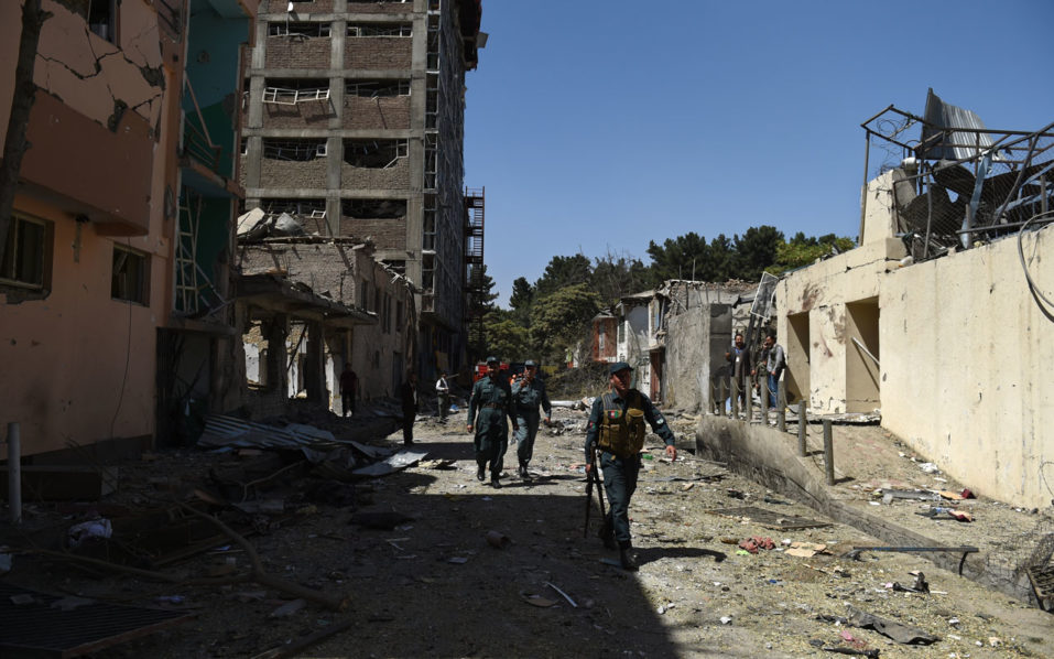 Afghan security personnel walk at the site following a car bomb blast that targeted the CARE International compound at Shar-e-Naw in Kabul on September 6, 2016. Explosions rang out during an hours-long attack on an international charity in Kabul, the latest assault in a wave of violence in the Afghan capital that has killed at least 24 people and wounded dozens. / AFP PHOTO / WAKIL KOHSAR