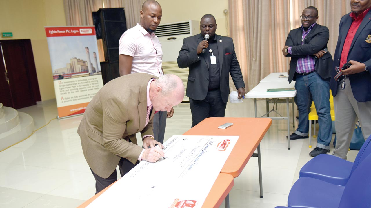 The Managing Director and Chief Executive Officer, Egbin Power Plc, Dallas Peavey Jr., signing the cheque for the award of scholarship to some students of Egbin and Ijede communities in Lagos State.