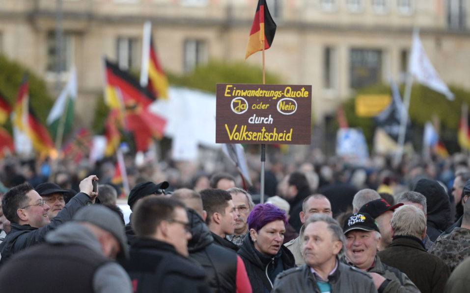 (FILES) This file photo taken on April 18, 2016 shows supporters of the PEGIDA movement (Patriotic Europeans Against the Islamisation of the Occident) holding a poster reading 'Immigration quota- yes or no- by referendum' during a rally in Dresden, eastern Germany.  Growing xenophobia and rightwing extremism could threaten peace in eastern Germany, voicing fears over the impact of a series of attacks against refugees in the region, warned the government on September 21, 2016. / AFP PHOTO / ROBERT MICHAEL