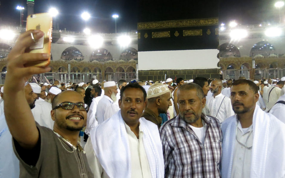 Muslim pilgrims take a selfie as they walk out following the last prayer of the day, leaving the the Grand Mosque in the Saudi holy city of Mecca, on September 7, 2016. The annual Hajj pilgrimage begins on September 10, and more than a million Muslims have already flocked to Saudi Arabia in preparation for what will for many be the highlight of their spiritual lives.  / AFP PHOTO / AHMAD GHARABLI