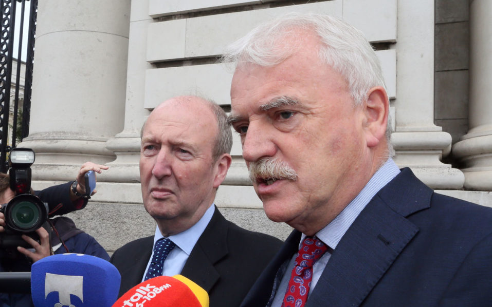 Independent Alliance Ministers, Shane Ross (L) and Finian McGrath speak to the press on arrival at Goverment buildings for a cabinet meeting in Dublin on September 2, 2016 on whether to appeal an EU order mandating Ireland to collect €13 billion in taxes from Apple. A crunch meeting of government ministers scheduled today was delayed in a last-ditch attempt to persuade a divided cabinet to back the appeal. The three independent ministers in the minority government have demanded a parliamentary debate on the issue and a review into how corporate tax is determined. / AFP PHOTO / PAUL FAITH