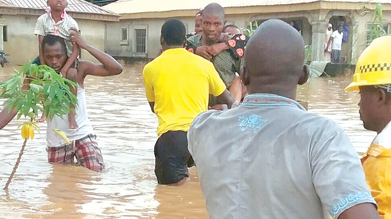 Residents wading through flood in Igando, Lagos