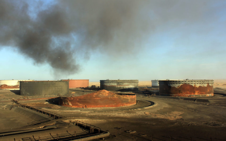 "(FILES) This file photo taken on January 8, 2016 shows smoke billowing from a petroleum storage tank after a fire was extinguished following fighting at Al-Sidra oil terminal, near Ras Lanuf in the so-called ""oil crescent"" along Libya's northern coast.  Forces loyal to General Khalifa Haftar on September 11, 2016 said they had seized the Al-Sidra and Ras Lanuf oil export terminals as the Tripoli-based Government of National Accord (GNA) struggles to assert its authority over the oil-rich country. Haftar's forces took the two terminals -- together capable of handling 700,000 barrels of oil per day -- from installation guards loyal to the GNA. The terminals had been closed for months following attacks in January by the jihadist Islamic State group, who took advantage of turmoil after the 2011 uprising to gain a foothold in the country.  / AFP PHOTO / STRINGER"