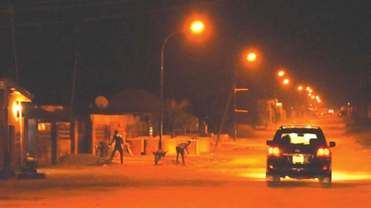 Construction work ongoing at night on a lit up street in Badagry