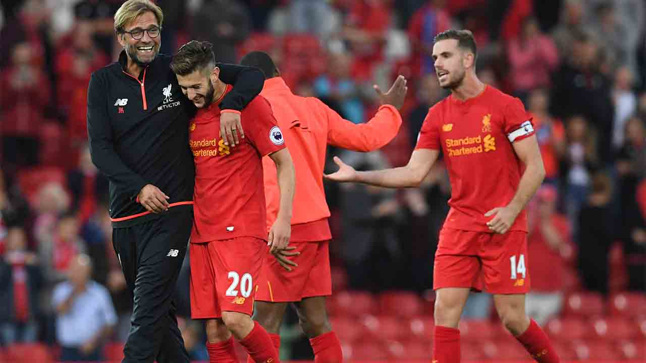Liverpool's German manager Jurgen Klopp (L) celebrates on the pitch with Liverpool's English midfielder Adam Lallana (2nd L) after the English Premier League football match between Liverpool and Leicester City at Anfield in Liverpool, north west England on September 10, 2016. Liverpool won the game 4-1. / AFP PHOTO / Paul ELLIS /