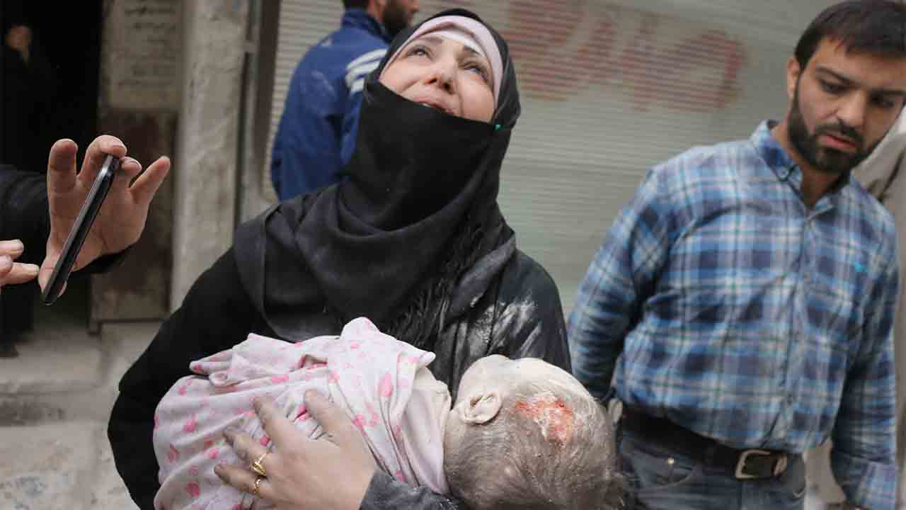 EDITORS NOTE: Graphic content / A Syrian woman carries the body of her infant after he was retrieved from under the rubble of a building following a reported airstrike on September 23, 2016, on the al-Muasalat area in the northern Syrian city of Aleppo. Missiles rained down on rebel-held areas of Syria's Aleppo, causing widespread destruction that overwhelmed rescue teams, as the army prepared a ground offensive to retake the city. / AFP PHOTO / THAER MOHAMMED