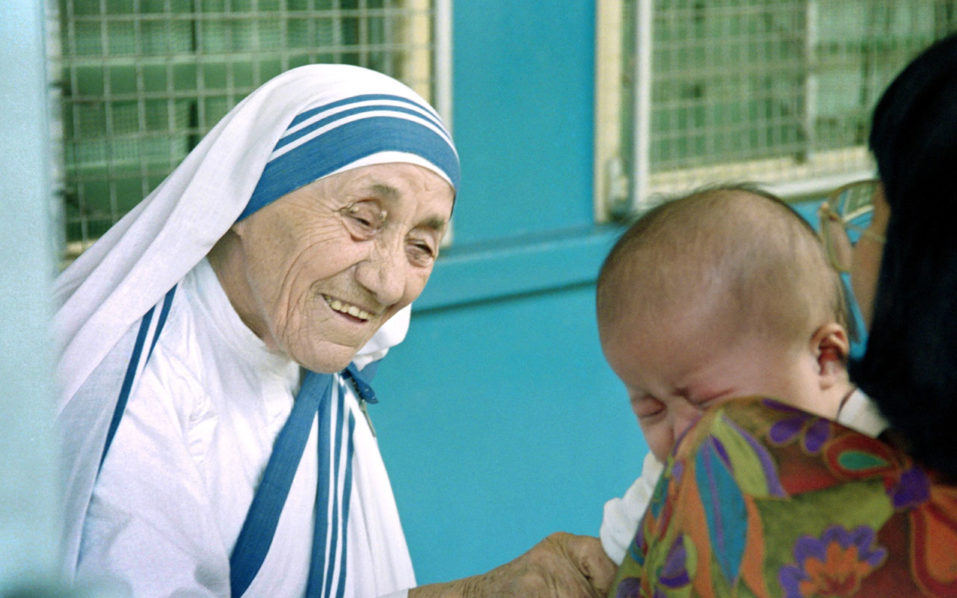 Mother Teresa (R) gives her blessing to a child at the Gift of Love Home on October 20, 1993 in Singapore. The 1979 Nobel Peace Price winner is on a stop-over while enroute to China where she will set up a fist home for Chinese handicapped children in Shanghai. / AFP PHOTO / Roslan RAHMAN