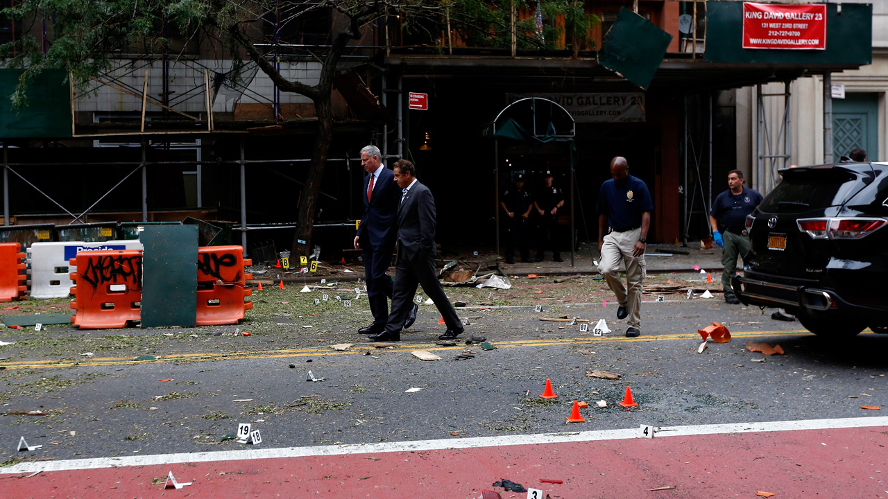 New York Mayor Bill de Blasio and New York Governor Andrew Cuomo tour the site of an explosion that occurred in the Chelsea neighborhood of New York on September 18, 2016. The bomb that exploded in New York September 17 wounding 29 people was an act of terrorism that has no apparent international link, the state governor said Sunday. / AFP PHOTO / POOL