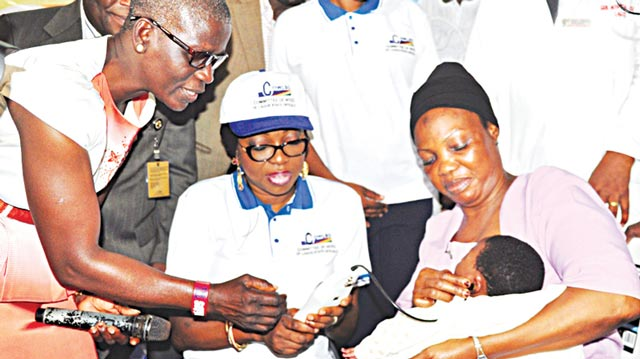Wife of Lagos State Governor, Mrs. Bolanle Ambode (middle) being assisted by Dr. Bolanle Badariyu (left) and matron, Mrs. Sanni Sekinat Adeola to carry out an ear test on baby Alli Yesir Alade during the commissioning of the newly upgraded Ear, Nose and Throat (E.N.T) department and sponsorship of surgery for goitre patients by Committee of Wives of Lagos State Officials (COWLSO), at the General Hospital, Odan, Lagos.