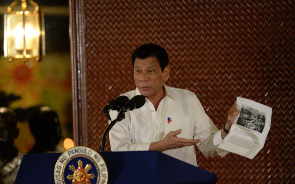 Philippine President Rodrigo Duterte holds up a photo and cites accounts of US troops who killed Muslims during the US's occupation of the Philippines in the early-1900s, during a speech at the Malacanang palace in Manila on September 12, 2016. Duterte ratcheted up his feud with the US on September 12, ordering all US special forces out of the southern Philippines where they have been advising local troops battling Muslim extremists. / AFP PHOTO / TED ALJIBE