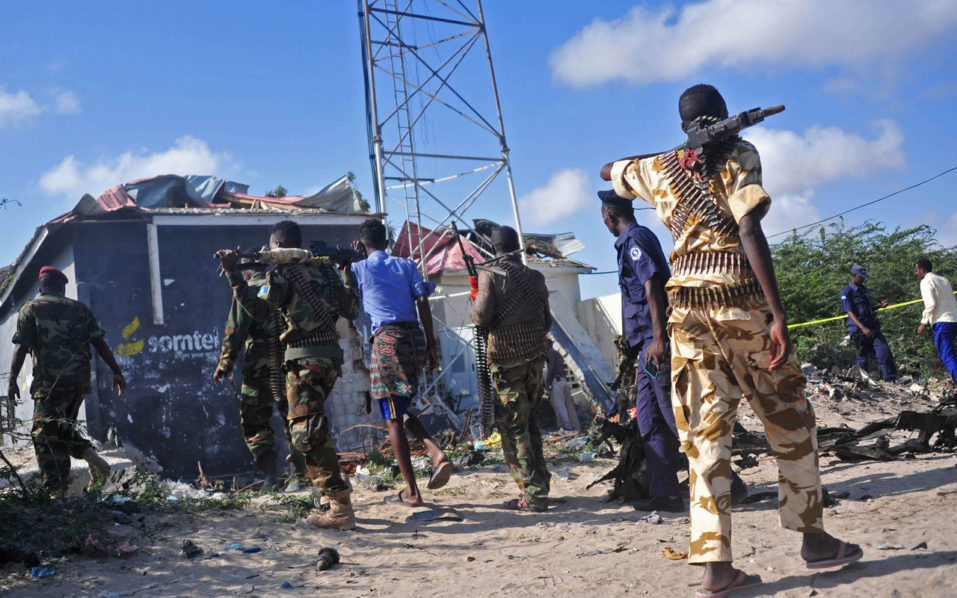 Members of the Somalian military forces walk at the site of a suicide car bomb attack, which killed a top Somalia general along with four of his security guards, near Gashandhiga compound, south of Mogadsihu, on September 18, 2016. General Mohamed Roble Jimale Gobale, known for fighting the jihadist Shabaab group, was killed on September 18 when a suicide bomber rammed an explosives-packed car into his vehicle, officials and witnesses said. The attack was claimed by the Al-Qaeda linked Shabaab. / AFP PHOTO / Mohamed ABDIWAHAB