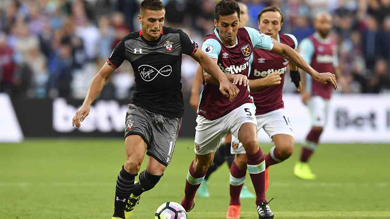 Southampton's Serbian midfielder Dusan Tadic (L) runs with the ball chased by West Ham United's Spanish defender Alvaro Arbeloa (R) during the English Premier League football match between West Ham United and Southampton at The London Stadium, in east London on September 25, 2016. / AFP PHOTO / Ben STANSALL / RESTRICTED TO EDITORIAL USE. No use with unauthorized audio, video, data, fixture lists, club/league logos or 'live' services. Online in-match use limited to 75 images, no video emulation. No use in betting, games or single club/league/player publications. /