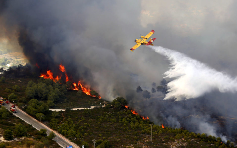A seaplane drops water over a wildfire next to a residential area along the coastline near the Spanish resort of Javea, Valencia region, on September 5, 2016. More than 1,000 people were evacuated after a wildfire fuelled by intense heat roared through brush surrounding a popular tourist resort on Spain's Costa Blanca, officials said today.  / AFP PHOTO / Manuel Lorenzo