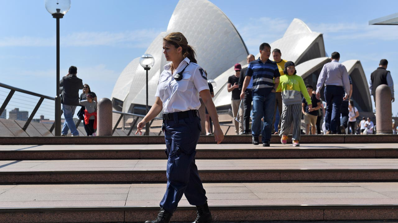 A security guard patrols the forecourt of the Sydney Opera House on September 9, 2016, after an 18-year-old man was charged after allegedly making threats at the Sydney Opera House, just days after the so-called Islamic State group urged followers to target high-profile Australian sites. Police said the teenager was spotted acting suspiciously in the forecourt of the building on Thursday, with reports that he was making extremist remarks. PHOTO: WILLIAM WEST / AFP